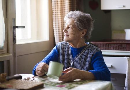 Oude vrouw drinkt thee in haar keuken in landelijke stijl