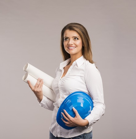 Portrait of Young woman architect with blue hard hat and paper plans, isolated on white background photo