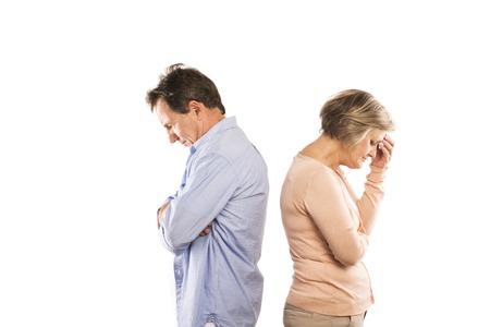 口論を白い背景の結婚の危機上で分離されて怒っている年配のカップルの撮影スタジオ