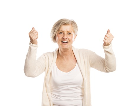Portrait of a happy senior woman saying yes and gesturing while isolated on white background photo