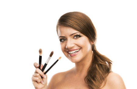 make up brushes: Beautiful woman putting make up on herself and holding make up brushes, isolated on white