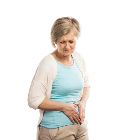 Senior woman with stomachache, isolated on white background photo