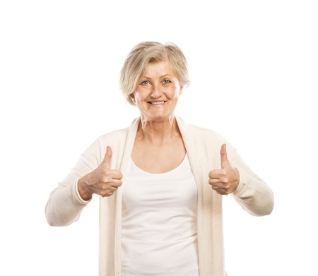 Portrait of a happy senior woman with thumbs up isolated on white background photo