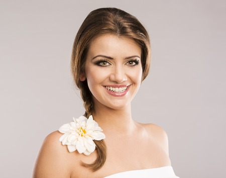 Portrait of beautiful woman with white flower in her hair  Isolate on grey background  photo
