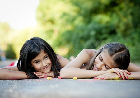 hopscotch: Two sisters laughing and playing with chalks on pavement in green sunny park Stock Photo