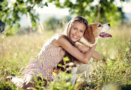 Portrait of a teenage girl with her beautiful dog outdoors photo