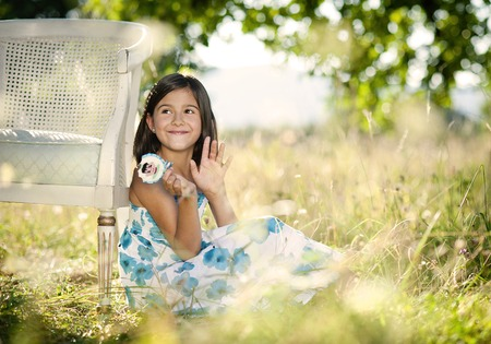 Cute little girl is enjoying leisure time with lollipop in green sunny park photo