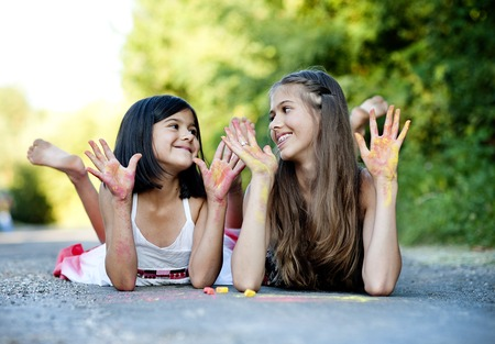 chalks: Two sisters laughing and playing with chalks on pavement in green sunny park Stock Photo