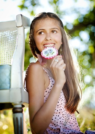 Beautiful teenage girl is enjoying leisure time with lollipop in green sunny park photo