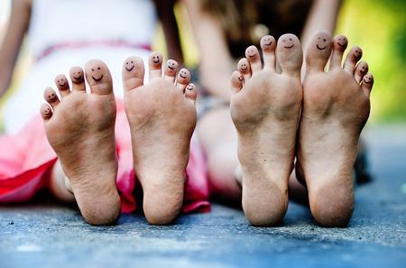 Grappig voeten van twee meisjes die op een stoep in groen park Stockfoto