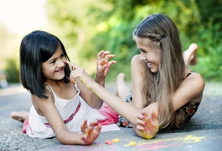 only 2 people: Two sisters laughing and playing with chalks on pavement in green sunny park Stock Photo