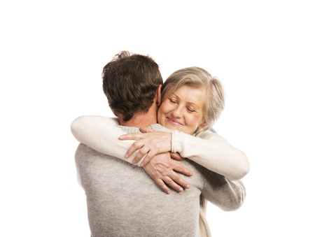 Studio portrait of happy seniors couple hugging  Isolated on white background  photo