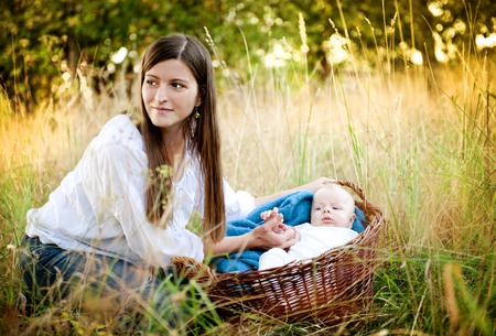 Happy young mother having fun with her baby son in nature photo