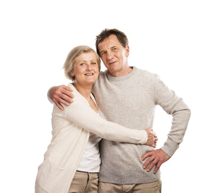 Studio portrait of happy seniors couple hugging  Isolated on white  photo