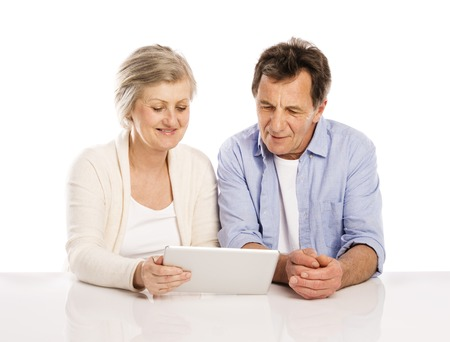 Senior couple using tablet, isolated on white background Фото со стока