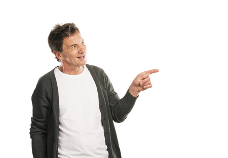 Portrait of a happy senior man pointing somewhere isolated on white background photo
