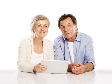 Senior couple using tablet, isolated on white background photo