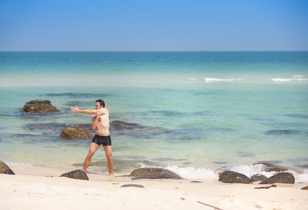 Handsome young man exercising at paradise beach in Phu quoc island, south of vietnam photo