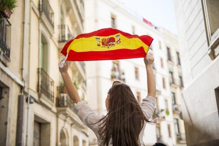 Gelukkige vrouw toerist loopt in de stad straat van Barcelon met Spaanse vlag Stockfoto