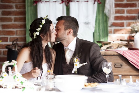 Bride and groom are eating at the wedding reception photo