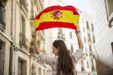 Happy woman tourist is walking in the city street of Barcelon with spanish flag