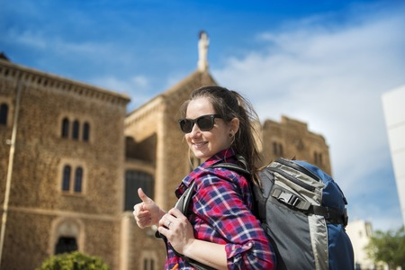 Pretty young female tourist with backpack in front of the church in Barcelona, Spain  photo