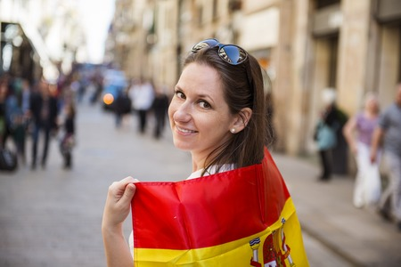flag spain: Happy woman tourist is walking in the city street of Barcelon with spanish flag