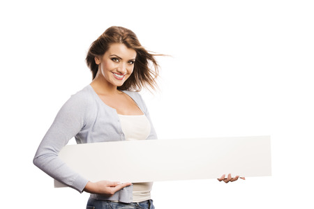Portrait of young happy woman with blank advertising board or copy space, isolated on white photo