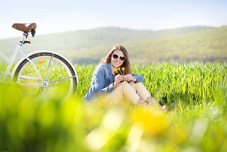 Pretty young girl with bike in green field Stock Photo - 27748371