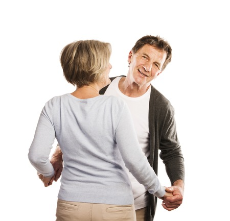 Studio portrait of happy seniors couple dancing  Isolated on white background  photo