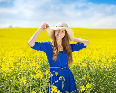 Happy young girl in blue dress and straw hat enjoying free time in yellow colza field photo