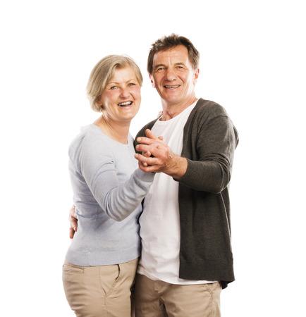 Studio portrait of happy seniors couple dancing  Isolated on white background  photo