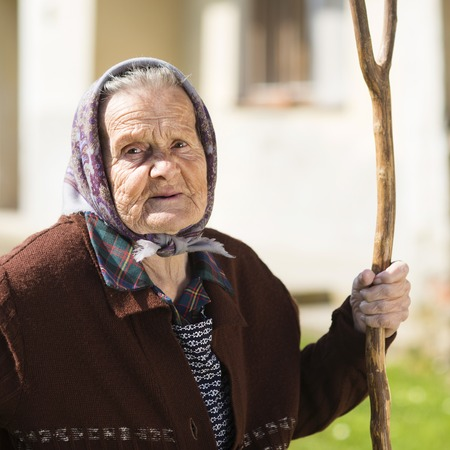 headscarf: Very old woman in head scarf with rake in her backyard