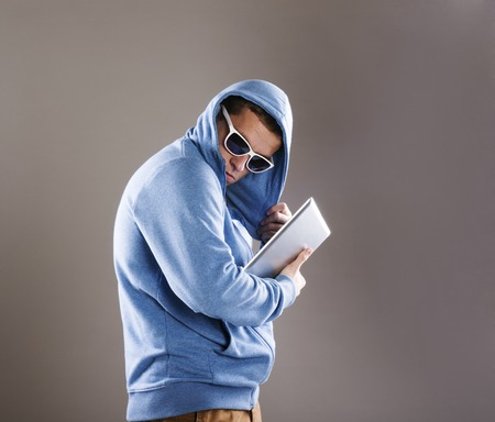 hidden danger: Dangerous man in mask with tablet on isolated background Stock Photo