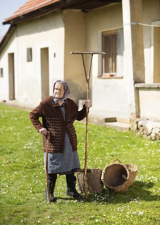 Very old woman in head scarf with garden tools in her back\ yard