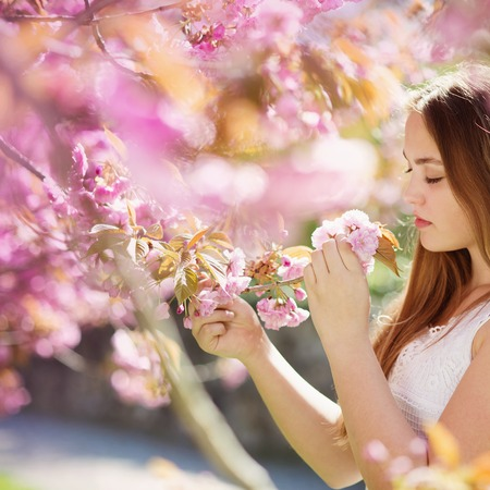 smells: Beautiful girl smells the flower