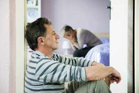 domestic: Mujer madura siiting en la cama tiene miedo de un hombre la mujer es víctima de la violencia doméstica y el abuso Foto de archivo