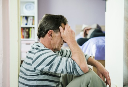domestic violence: Mature woman siiting on the bed is scared of a man  Woman is victim of domestic violence and abuse