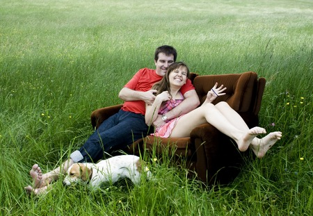 Happy young couple relaxing and having fun on the couch at the green field photo