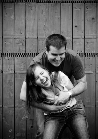 Black and white portrait of happy young couplehaving fun in front of fence in garden photo