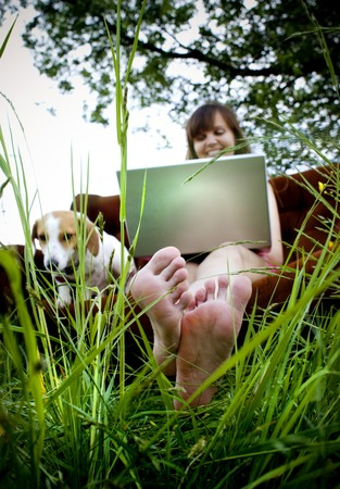 Woman using laptop on couch in sunny field in countryside photo
