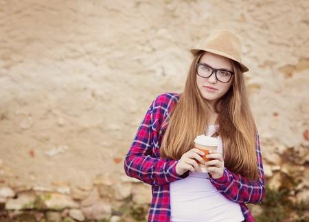 Teenage hipster girl enjoying her take away drink walking down the city street photo