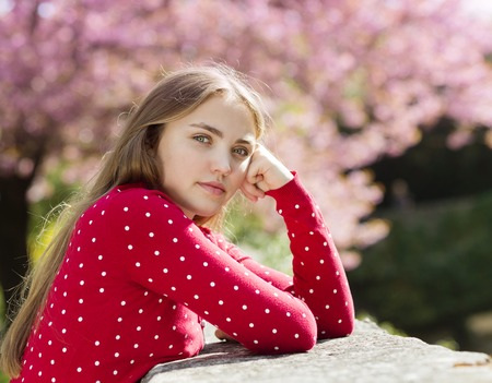 red cardigan: Beautiful girl in red cardigan lying relaxing in spring garden with blooming trees