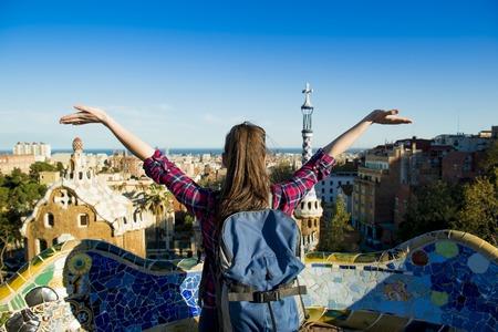 Achter mening van jonge vrouwelijke toerist genieten van het uitzicht in Parc Guell in Barcelona, Spanje