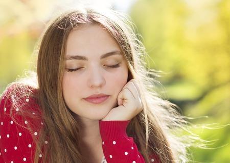 red cardigan: Portrait of beautiful girl in red cardigan daydreaming in green prak Stock Photo