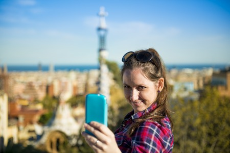 guell: Pretty young female tourist takes selfie in Parc Guell in Barcelona, Spain