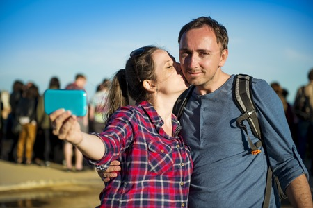 Happy young tourist couple looking at camera and taking selfie, smiling and having fun on Europe vacation trip in Barcelona, Spain  photo