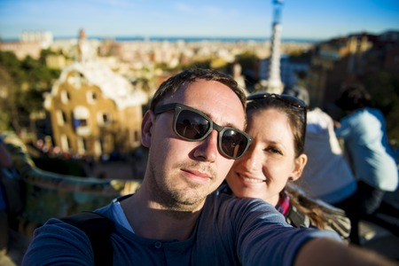 Happy young tourist couple looking at camera and taking selfie in Parc Guell, Barcelona, Spain  photo