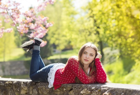 red cardigan: Beautiful girl in red cardigan lying on a wall in spring garden with blooming trees