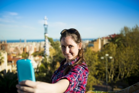 Pretty young female tourist takes selfie in Parc Guell in Barcelona, Spain  photo